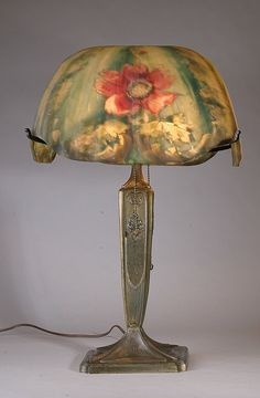 This exquisite Pairpoint ribbed lamp has two floral panel-like paintings wit ha predominantly teal-green to varying lighter green background. There are two large fuchsia and pink flowers and several flower buds. The Torino shade is signed and the base is signed.