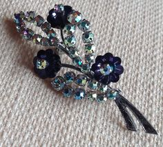 Stunning Vintage Diamante Brooch in fabulous condition - looks unworn. Very pretty indeed with extremely sparkly cut rainbow glass small stones and dark blue/ purple tone glass flowers. The base of the silver tone stems are also embossed with a delicate and intricate design. It has a sturdy rollover safety clasp. A real statement piece.