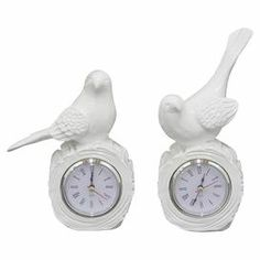 """Bring eye-catching appeal to your desk or mantel with these lovely table clocks, showcasing bird-inspired silhouettes and a crisp white finish.  Product: Small and large table clockConstruction Material: Resin and glassColor: WhiteFeatures: Bird-inspired silhouettesAccommodates: Batteries - not includedDimensions: Small: 7"""" H x 3.25"""" W x 4"""" D  Large: 8.25"""" H x 3.75"""" W x 5.25"""" D"""