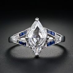 Here is a rare and unique, original Art Deco engagement ring for a rare and unique woman. Not a round diamond, not an emerald cut diamond, but a distinctive, bright white lozenge, or diamond shape (as in playing cards) diamond weighing 1.10 carats. The distinctive diamond is seated atop a diamond set under gallery and is embellished by sapphire and diamond 'V' shape epaulets. A simply gorgeous, one-of-a-kind estate diamond engagement ring, circa 1930s. Platinum
