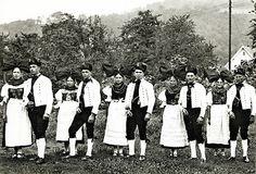 """""""Paare in Tracht aus dem Hanauer Land, um 1938"""", in: Historische Bilddokumente <http://www.lagis-hessen.de/de/subjects/idrec/sn/bd/id/112-009> (Stand: 5.9.2012). Charakteristisch für die Frauentracht ist das Fransentuch über der Brust und die große Flügelhaube. Die Trachten sollen aus dynastischen Gründen (das rechtsrheinische Hanauer Land fiel 1803 an Baden) teilweise elsässisch geprägt sein. #Hanau"""