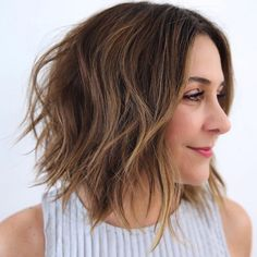This long bob cut gets its shape from layers that are slightly shorter in the back and from pieces left longer in the front. If you're looking for a no-heat solution to waves, spray hair with a salt spray, then braid just the top half of your hair. Leave in for a few hours, then deconstruct.