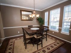 The formal dining is well lit with a wall of windows and special touches such as chair railing, crown molding, and hardwood floors.