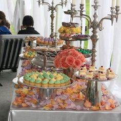 Dessert table. Baking trays on top of buckets. Flower petals (color coord.) and candelabras
