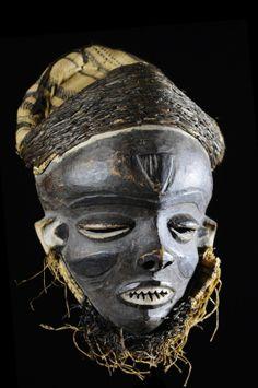 """Les masques Mbuya, tel ce très bel exemplaire années 50, sont caractéristiques du style Katundu, par lequel l'art Pende s'est fait connaître. Visage triangulaire et convexe, paupières lourdes baissées, triangulaires elles aussi, et une ligne de sourcils formant un """"V"""". On peut encore noter un nez généralement retroussé avec des narines largement ouvertes et une bouche dentée. Les masques dit """"Mbuya"""" intervenaient autrefois dans les rituels de circoncision. ..."""