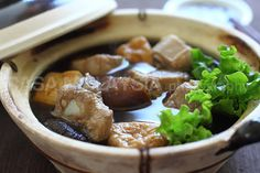Bak Kut Teh (Pork Bone Tea Soup) is a Chinese-inspired soup dish. Infused with herbs such as dong quai, cinnamon, star anise, it's loaded with pork ribs, dried Shiitake mushrooms, tofu puffs, and heaps of garlic--permeating the kitchen with evocative, mouth-watering aromas. Bah Kut Teh needs a couple hours of slow boiling and the end result is rich concoction perfumed with a sweet herbal and earthy flavor. It's best cooked and served in a clay pot! ENJOY!!