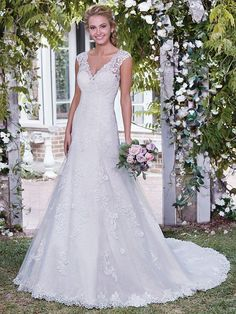 Rebecca Ingram - PATRICIA, Beautiful lace appliqués waltz over the bodice, skirt, and hemline of this classic A-line wedding dress, with sheer lace comprising the illusion V over sweetheart neckline, cap-sleeves, and V-back. Finished with covered buttons over zipper closure.