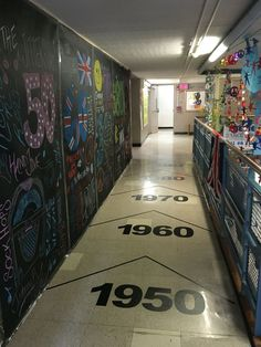 Dance through the decades, decorated hallway. Chalkboard paper panels on left. Hanging string of themes items on right, vinyl records, cut out Beatles, peace signs, neon Slinkis, CDs , 1950,1960,1970,1980,1990 . Dance through the decades