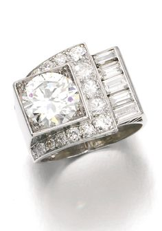DIAMOND RING, 1930S Of geometric design, set with a circular-cut diamond weighing 2.48 carats, within a surround of similarly cut and baguette diamonds