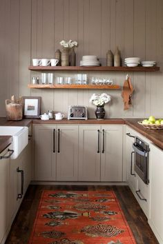 Cozy U-shaped kitchen with open shelving by Altlanta-based Carter Kay Interiors (via Desire to Inspire).