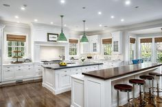 This white on natural wood kitchen layout features two islands; one marble topped with secondary sink, the second with raised wood countertop for dining.