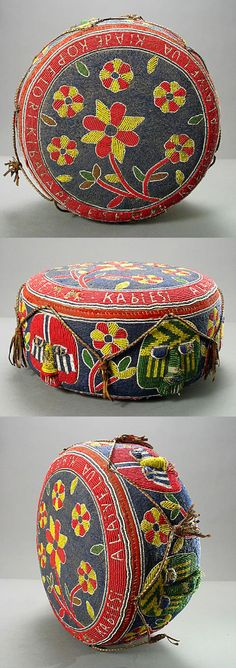 Africa | Oba's beaded cushion/footstool from the Yoruba people of southwestern Nigeria | 20th century | The six faces encircling the side panel represent orisa (deities) which the king is able to utilize or control. Around the rim the king's name is inscribed in white. Leather tassels cover lovely flowers with curved stalks alternating between the faces.