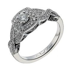 A round solitaire lies at the heart of this striking Neil Lane ring, surrounded by an elegant halo and sparkling, diamond set crossover arms totalling 69 points. Finished with elegant milgrain detailing, this exquisite ring boasts an indulgent vintage inspiration. This engagement ring has a matching wedding band under code 1350382.