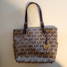"""Michael Kors Monogram Jet Set EW Signature Tote NWT!! Michael Kors stylish everyday signature fabric tote. Beige/Ebony/Mocha/Gold. Leather trim. Double handles with 8"""" drop. no closure. 2 open side pockets. Interior features center divider zip compartment; back zip pocket; two slip pockets; cell phone pocket; key fob. MICHAEL Michael Kors Bags Totes"""