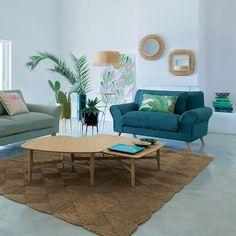 Un salon tropical dans les moindres détails. Voici un salon qui a su adopter le style tropical de façon subtile et ce dans les moindres détails. Des cache-pots en céramique aux couleurs pile dans l'air du temps, des plantes grasses, un tapis en vannerie de jacinthe d'eau, des miroirs en rotin et un joli imprimé feuillage pour les coussins : c'est un sans-faute.