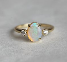 Beautiful simple oval opal ring with 2 diamonds on each side of prong set opal. Product details Middle gemstone Gemstone: Opal (If you prefer a