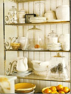collection of iron stone and yellow ware, cloches and bird nests and eggs all resting on an antique baker's rack....