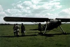 """A commander departs with two staff officers. The situation maps and papers suggest that they have just attended a situation conference. The Fieseler Fi 156 C """"Storch"""", manufacturer's code GK+M?, wears the yellow fuselage band for aircraft operating on the Eastern Front. The photograph was taken in Russia in the summer of 1941 or 1942."""