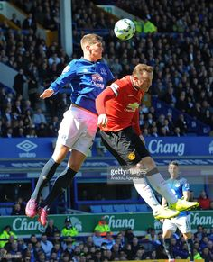 John Stones (L) of Everton rise for the head ball with Wayne Rooney of Manchester United during the Barclays Premier League match between Everton and Manchester United at Goodison Park