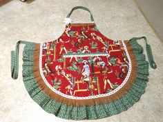 """Just finished making this """"Annie Oakley"""" apron with pinup cowgirls and horses! The ruffle and ties are made with a green arrow print and it's trimmed with faux leather fringe and lace!"""