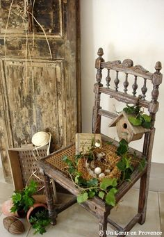 A broken cane chair and a door have spring time decorations added.