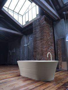 Vrijstaand bad in badkamer met industrieel interieur