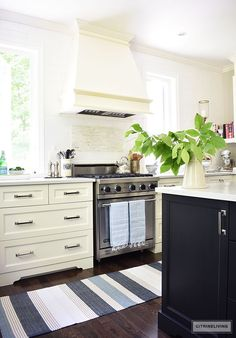 White kitchen decorated for Summer with blue and white ginger jars and dishes accented a blue and white striped rug and turkish towels and fresh cute greenery.