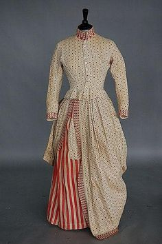 An unusual printed cotton Independence day dress, circa 1876, of inexpensive striped and spotted calico trimmed with red and white lace, the un-boned bodice with stand collar, short tabs to the back, over draped and polonaised skirt, bust 86cm, 34in, waist 71cm, 28in (2)