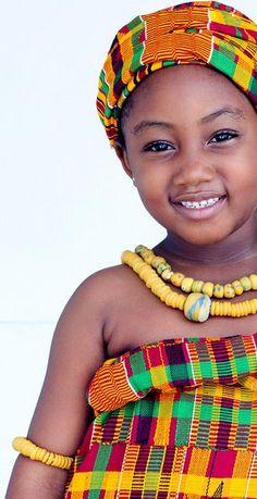 An African child shows her beauty in a traditional Ghanaian outfit. UN HERMOSO ROSTRO Y UNA BELLA SONRISA DE NIÑA.