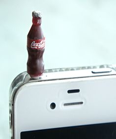 this phone plug/dust cover features a miniature coke bottle. it measures 2cm tall. This dust plug is compatible with iphones, ipads, ipods, Samsung, HTC, and all other electronic devices with ear plug