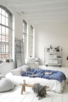 The lofty industrial bedroom. Industrial windows and ceiling, this all white bedroom has the trendy and hip feel.