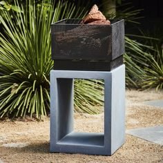 This square firepit in grey is perfect for entertaining guests in any outdoor space.