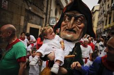A man dressed as a giant holds a young girl during the giants and big heads parade of the San Fermin festival in the Northern Spanish city of Pamplona. (AFP)