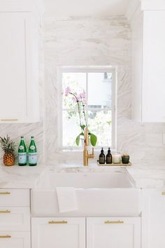A sleek kitchen with a small dish window, gold hardware, white cabinents, and marble backsplash