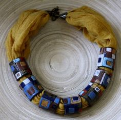 I love the 'presence' of this necklace, and because most of the mass is fabric, it's light, but the polymer rings give it definite interest. Does anyone know who the artist is?