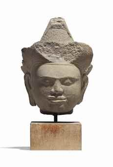 A SANDSTONE HEAD OF A MALE DEITY CAMBODIA, KHMER, ANGKOR WAT PERIOD, 12TH CENTURY Carved with a faint smile playing around his lips, with almond-shaped eyes below ridged eyebrows, wearing an elaborate crown, his hair worked in a stylised chignon, on wood stand 7 ½ in. (19 cm.) high