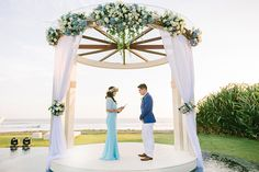 Romantic green and white wedding arch with bride and groom dressed in white and blue // Yoska and Nariza capped off their week-long celebrations with a bang with a sunset ceremony and dinner reception held at Phalosa Villa, Seminyak, Bali, shot by Haniff Hazim of Wedlocx and planned by Bali Berdua. The couple hosted an intimate, travel-themed destination wedding for their closest friends and family, complete with an encore performance of the flash mob number they performed