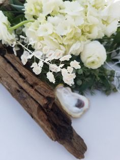 Gorgeous wedding reception with Oyster Shell and driftwood accents.  Centerpieces white flowers ideas, gold accents and dried flowers decked the gorgeous white tables.  At Last Florals 30a wedding designer Rosemary Beach Seaside