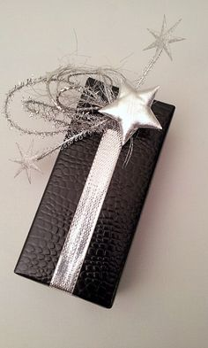 gift wrap - easy - small silver ribbon with loops of diff.cord & wire snippets, ends with little silver stars - http://la-couronne.de/
