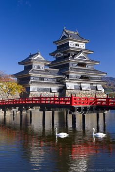 Japan - Matsumoto-jo (Matsumoto Castle), the three-turreted donjon built in 1595 in contrasting black and white, surrounded by a moat with access across ornate...