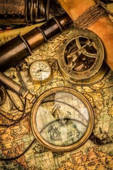 antique maps: Vintage magnifying glass, compass, telescope and a pocket watch lying on an old map.