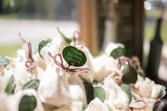 """Wedding Favors. These are handmade burlap sacks containing coffee grounds. Each sack is topped with a """"Thank you for coming"""" message written on a silver dollar eucalyptus leaf."""
