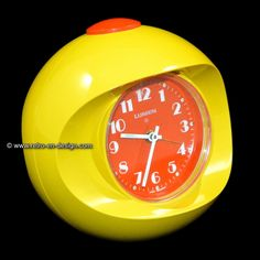 Vintage 60s/70s Space Age alarm clock This ball-shaped alarm clock from West Germany is a great example of the Spage Age Design era. This bright yellow alarm clock has an orange alarm button with an orange dial. The white numerals and hands have fluorescent details that glow in the dark.  http://www.retro-en-design.co.uk/a-45810533/plastics/vintage-60s-70s-space-age-alarm-clock/