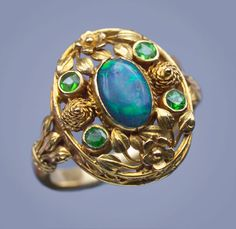 Superb Arts & Crafts ring, attributed to Henry Wilson, gold set with black opal and demantoid garnets, ca. 1900