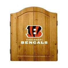 This NFL Cincinnati Bengals Wooden Dartboard Cabinet Set is made of solid  pine and makes a great gift for the sports fan in your life. This  officially licensed dartboard comes with mounting hardware and six team  logo darts.   Great gift for sports fan Perfect for man cave or garage Made by Imperial International Solid pine wood dartboard cabinet All natural 18-inch bristle dart board Mounting instructions and hardware included Six steel darts with team logo on flights Includes chalk and…
