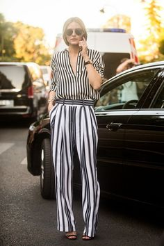 Olivia Palermo wears a striped button-down blouse, striped trousers, and strappy heels