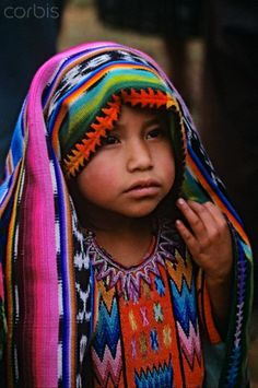 A Guatemalan girl, the daughter of a shaman, during a Mayan rite to ask forgiveness from the Earth for digging in search for bodies The site is blessed for good fortune during the ceremony.