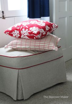 Thick, grainy linen cotton slipcover trimmed in red for a classic ottoman. A sweet little spot to put your feet up at the cottage.