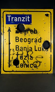 """""""Snipers Alley"""" sign near the Sarajevo airport in Bosnia-Herzegovina. The sign is damaged from bullet and mortar holes. On exhibit at the Newseum in the Time Warner World News Gallery.  Loan, David Rust, CNN"""