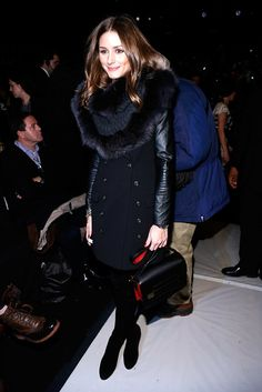 Working a leather-sleeved trench, fur snood, and suede boots at Carolina Herrera's show in NYC, Olivia prov...